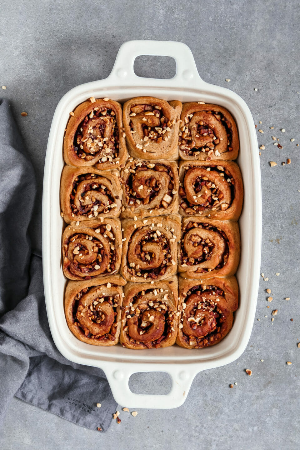 Vegan cinnamon buns with a sweet apple nut filling served in a baking form.