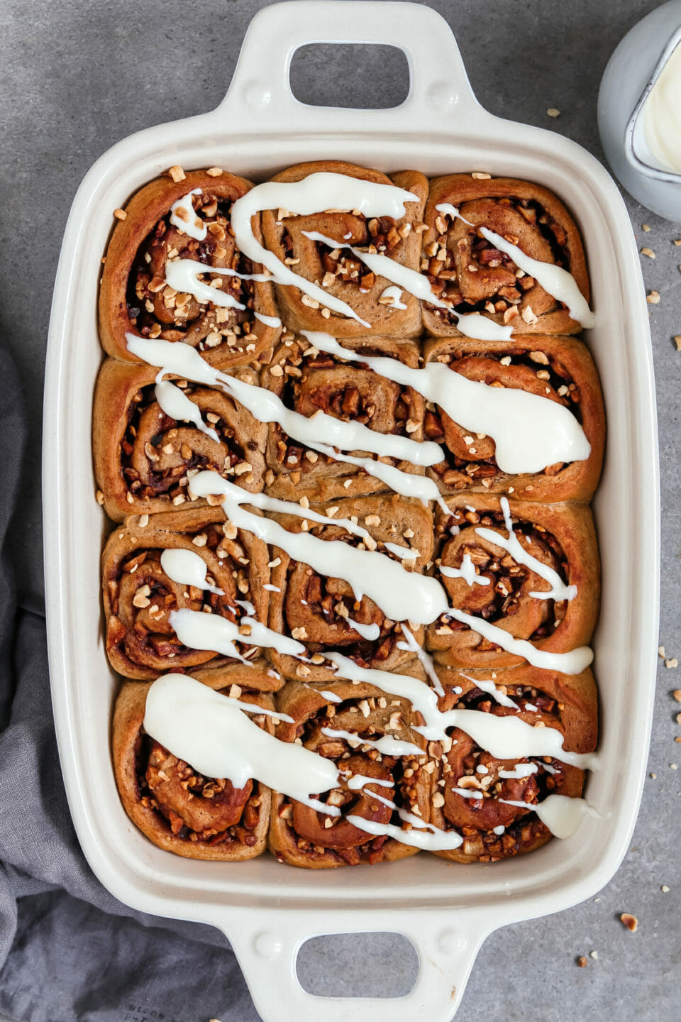 Vegan cinnamon buns with a sweet apple nut filling and cream cheese frosting served in a baking form.