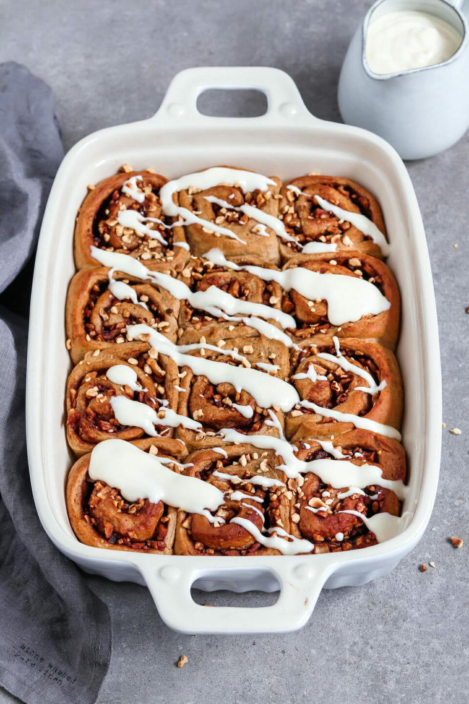 Vegane Zimtschnecken Rollen mit Apfel Zimt Füllung und einem Cream Cheese Frosting. Platziert sind die Zimtschnecken in einer Auflaufform.