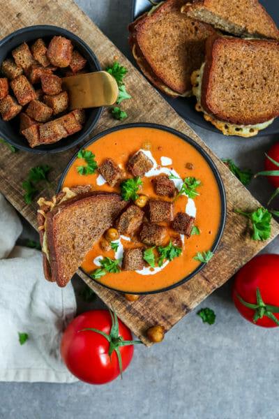 Cremige Tomatensuppe serviert mit Kokosnussmilch, Croutons, Käse Sandwich und knusprigen Kichererbsen.