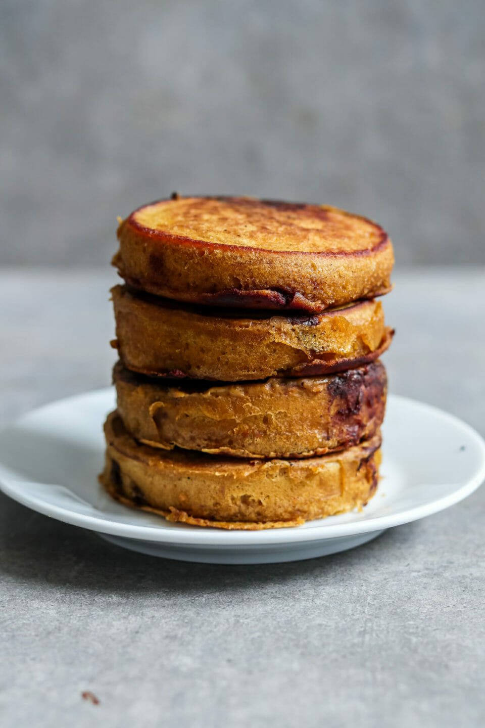 Vegan pancakes with pumpkin and chocolate drops. Served with caramelized brazil nuts and maple syrup.
