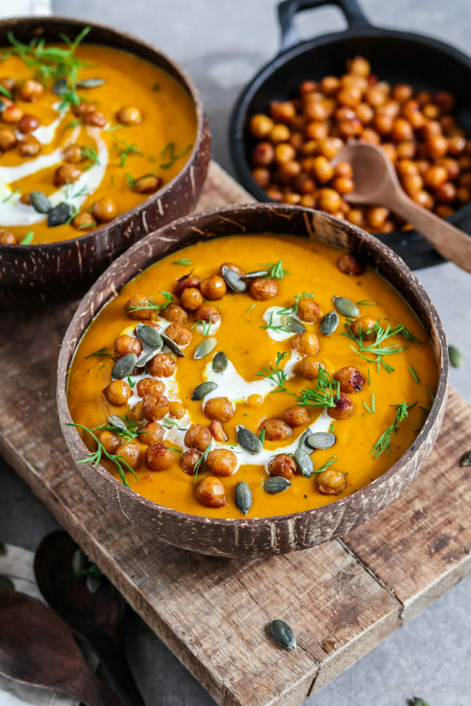 Creamy pumpkin soup served with coconut milk, chickpeas and pumpkin seeds