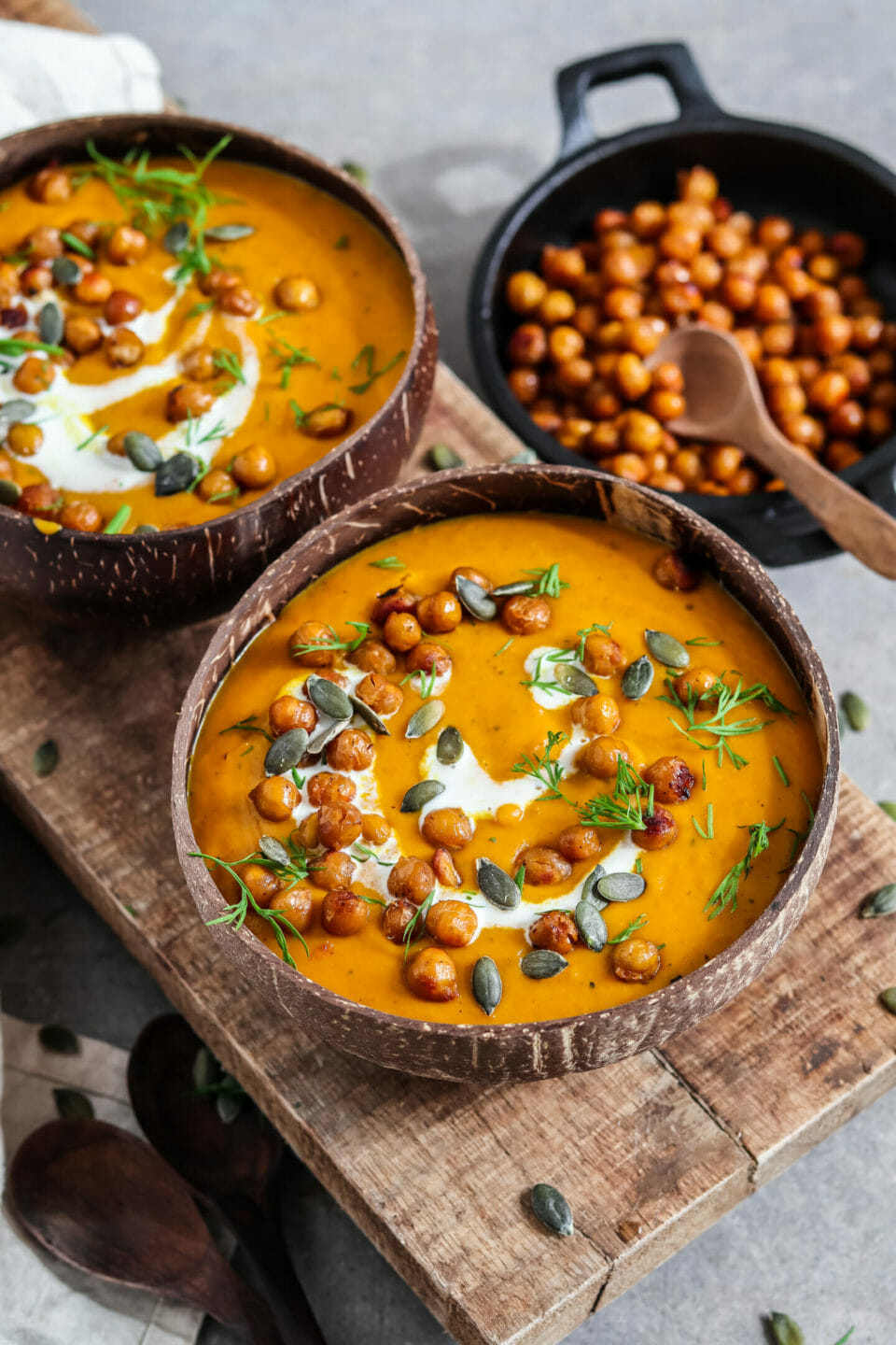 Creamy pumpkin soup served with coconut milk, chickpeas and pumpkin seedsa