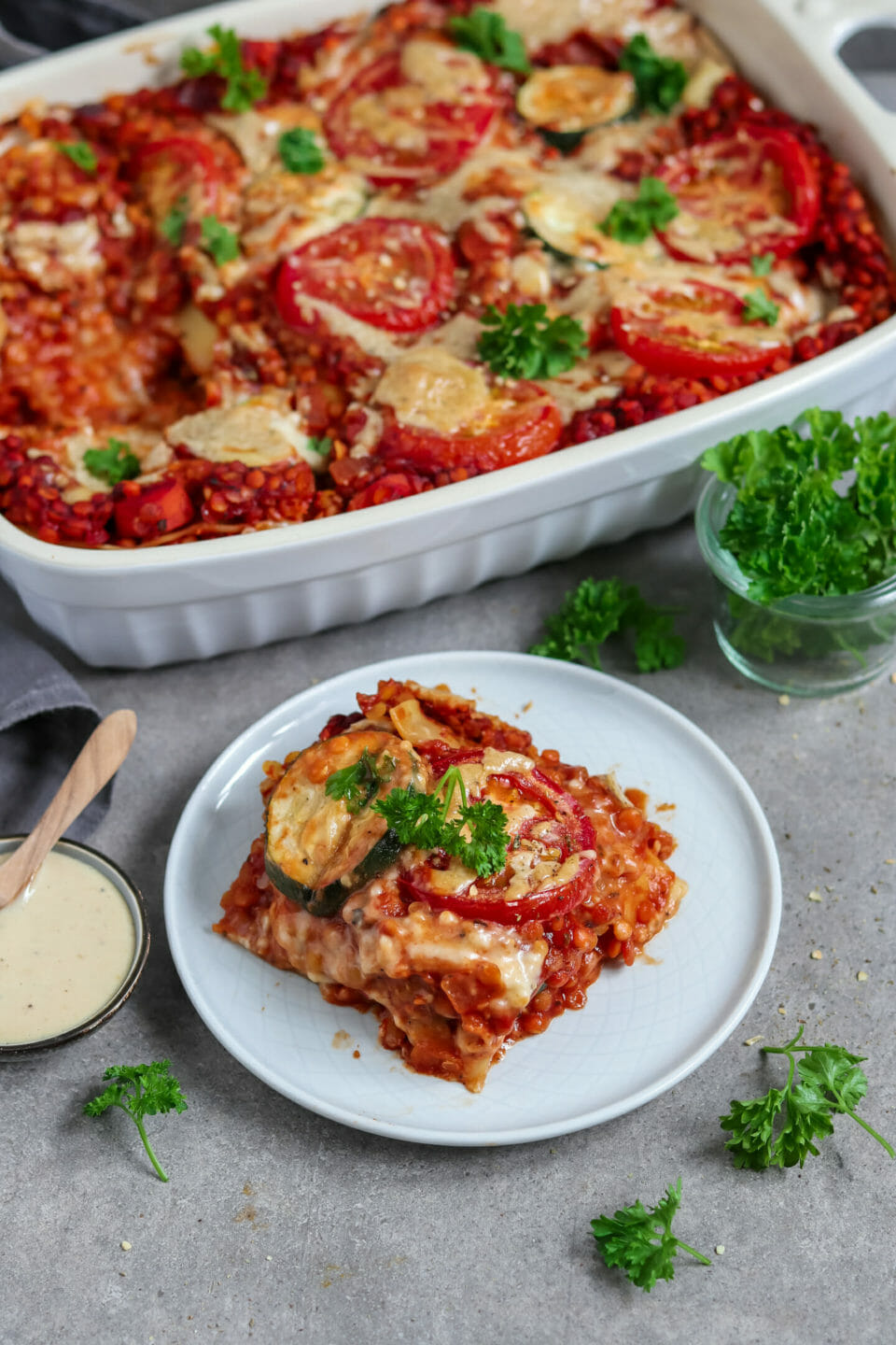 Vegan lasagna made of red lentil bolognese, lasagna sheets, zucchini, béchamel sauce and homemade cheese sauce