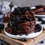Fluffige Schokoladen Pancakes mit Blaubeeren und Banane serviert mit Schokoladen Sauce, Brombeeren, Beeren Kompott und gefriergetrockneten Beeren