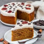 Veganer Kürbis Kuchen (rund gebacken) mit einem cremigen Zimt Frosting und dekoriert mit Pekannüsse und Schokoladen drops.