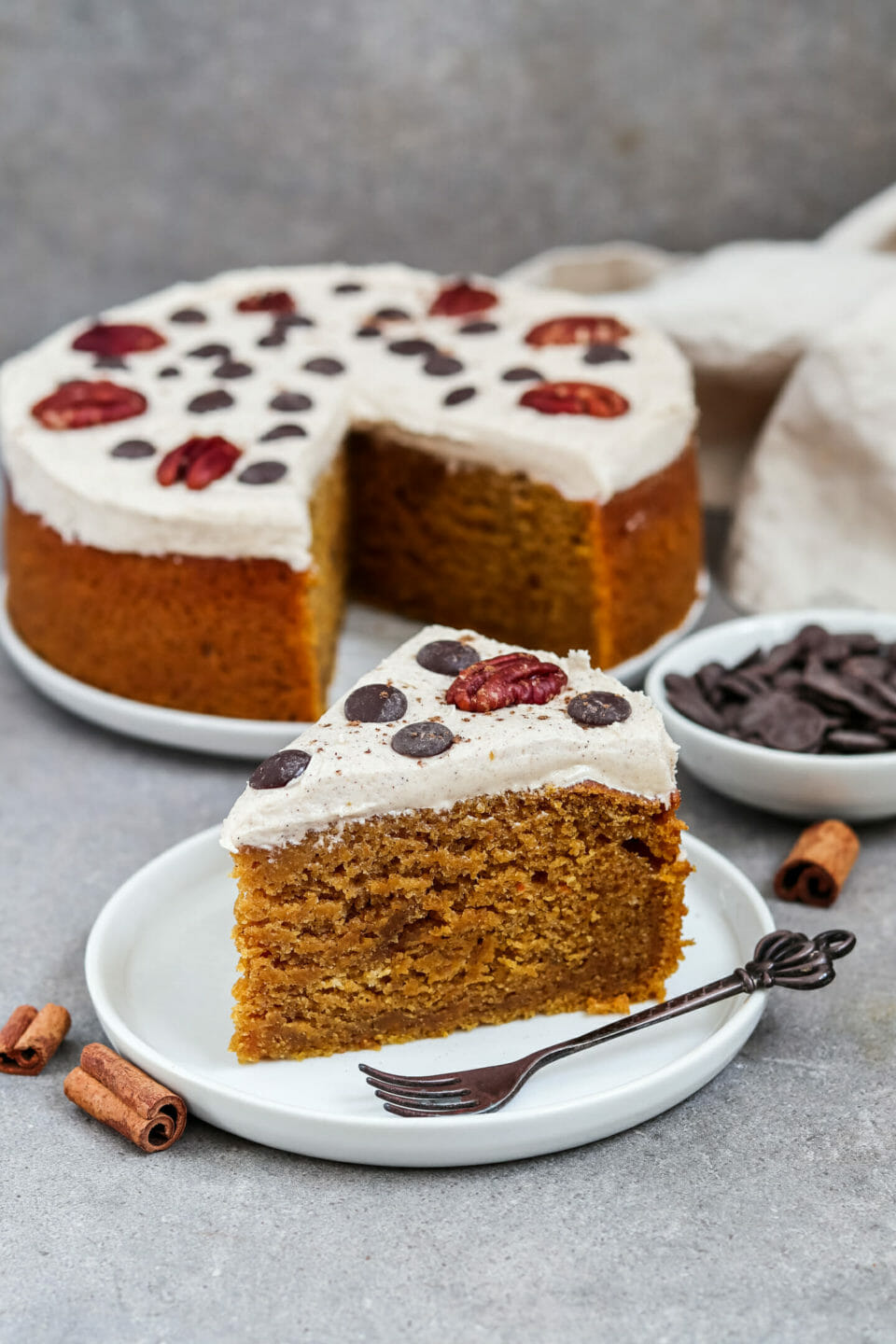 Vegan pumpkin cake with creamy cinnamon frosting and decorated with pecans and chocolate chips.