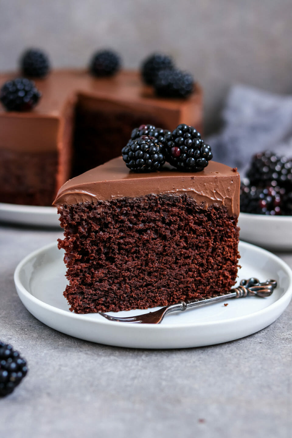 Fluffy chocolate cake with creamy chocolate frosting and blackberries.