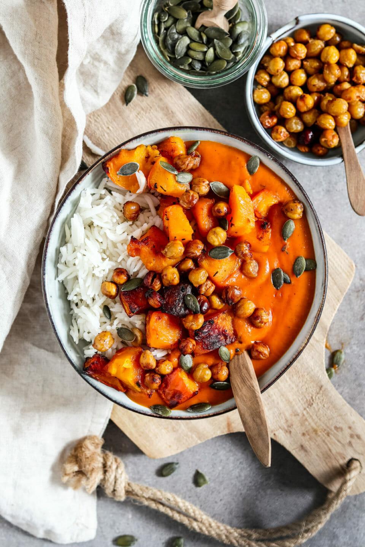 Cremiges Kürbis Curry serviert mit Reis, geröstetem Kürbis, knusprigen Kichererbsen und Kürbiskernen.