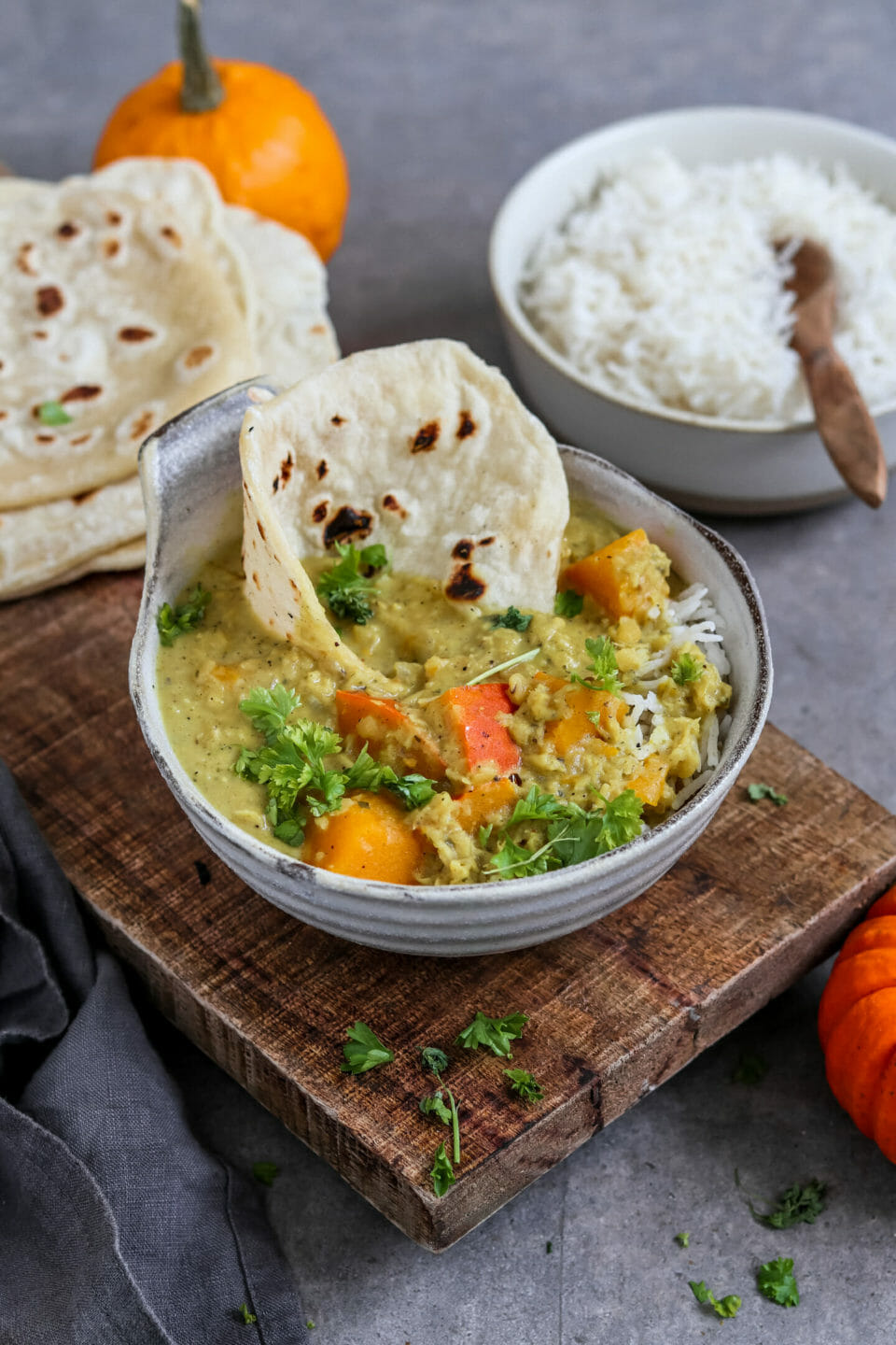 Vegan lentil curry with pumpkin served in a bowl with rice and homemade naan bread.