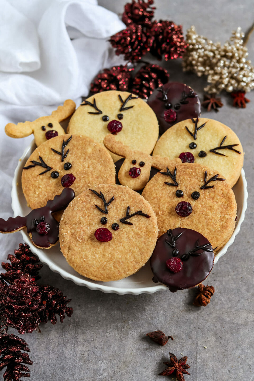Runde Doppelkekse gefüllt mit einer selbst gemachten Schoko Nuss Creme und dekoriert als Rentiere mit roten Cranberry Nasen.