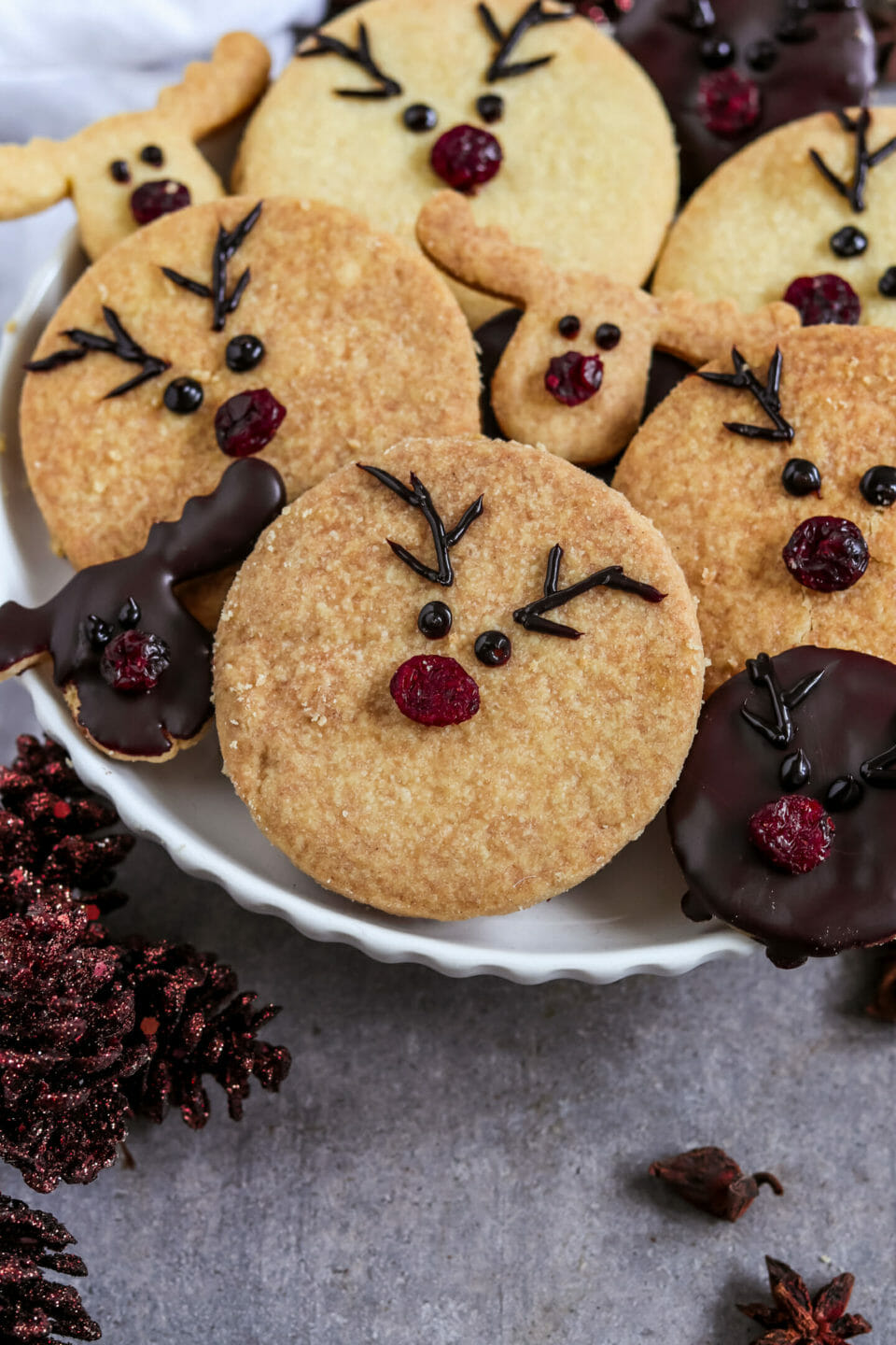 Round Double cut out cookies filled with homemade chocolate nut spread and decorated as reindeers with red cranberry noses.