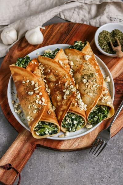 Vegane Pfannkuchen gefüllt mit einer Spinat Feta Füllung, gebacken im Ofen und getoppt mit veganer Feta und gerösteten Pinienkernen.