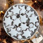 Vegane Zimtsterne auf einem Dessertteller mit weihnachtlicher Dekoration.