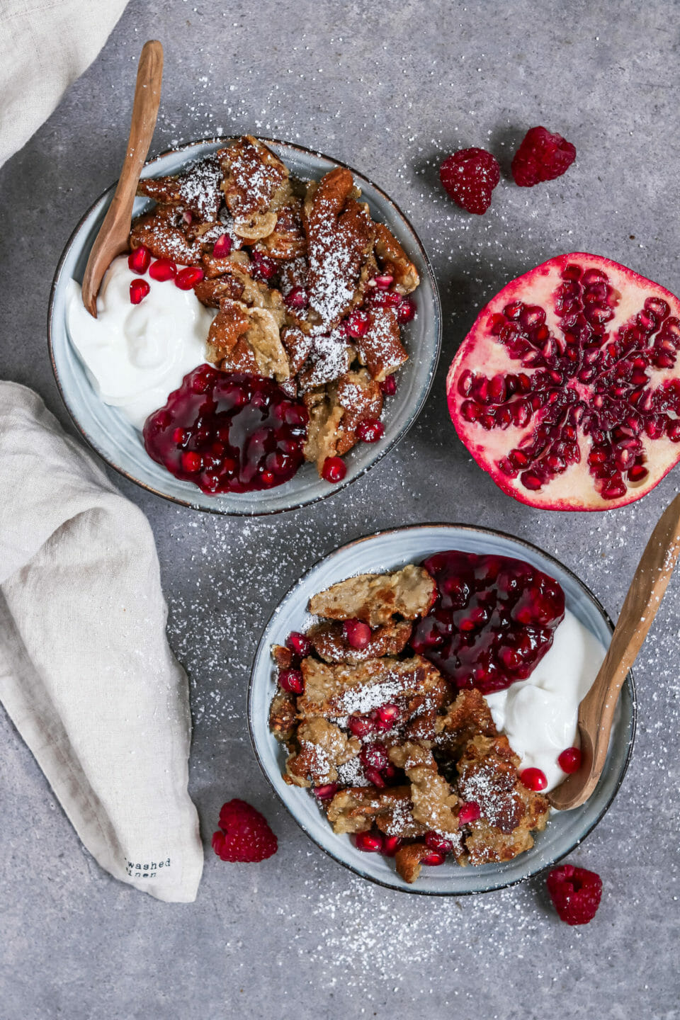 Vegan Kaiserschmarrn (scrambled pancakes) served in two bowls with berry compote and vegan yogurt.