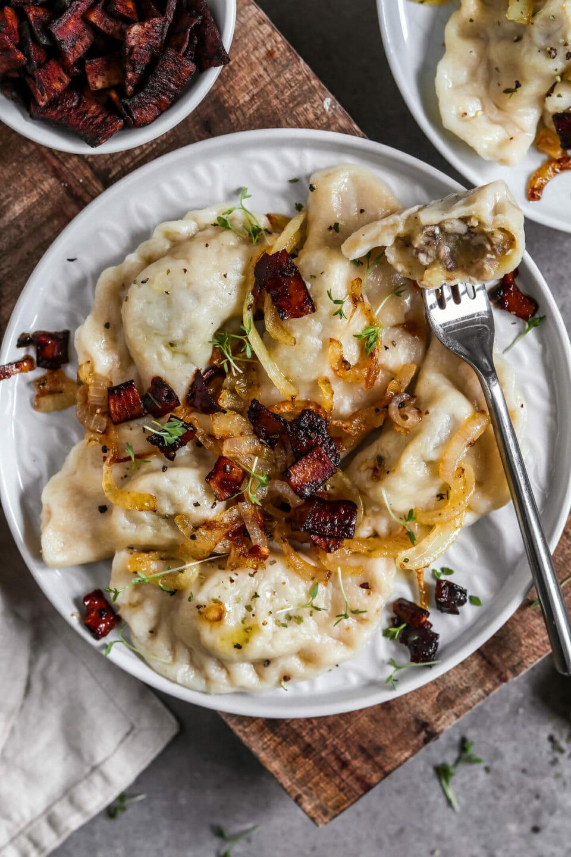 Vegane Piroggen gefüllt mit Pilzen serviert auf einem Teller mit veganem Kokos Speck und gebratenen Zwiebeln.