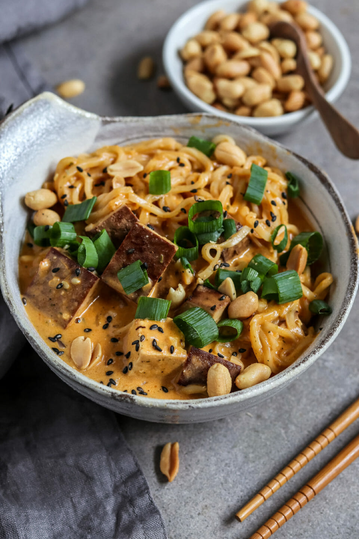 Vegane Thai Nudelsuppe mit Tofu, Frühlingszwiebeln und geröstetem Sesam. Nahaufnahme.