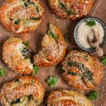 Sesam-Laugenbrezel gefüllt mit Spinat und Käse, serviert auf einem Holzbrett.