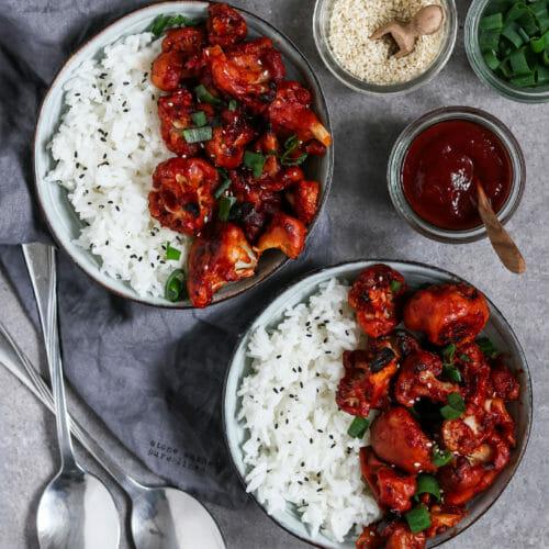 Vegane Blumenkohl Wings serviert mit Reis, Sesam und Lauchzwiebeln.