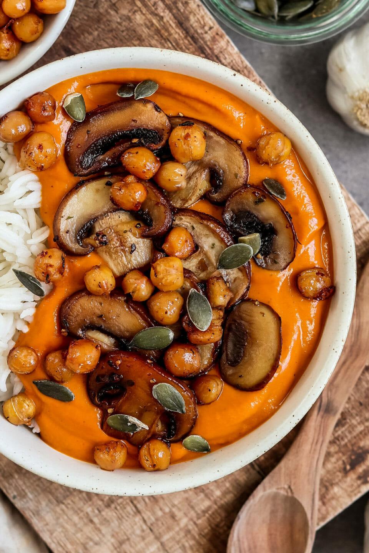 Veganes Garam Masala Curry serviert mit Reis, knusprigen Kichererbsen, Champignons und Kürbiskernen. Seitliche Ansicht.