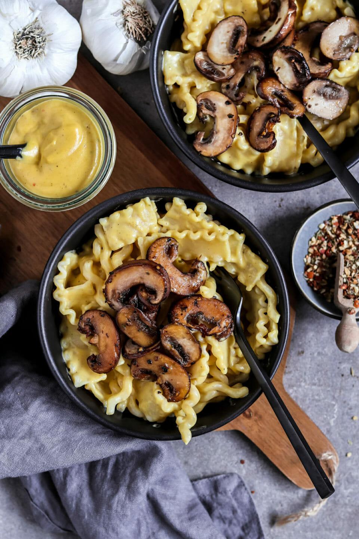 Veganes Mac n Cheese mit gebratenen Champignons serviert in zwei Schalen.