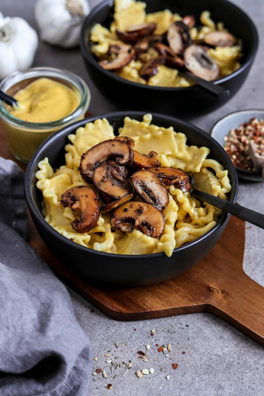 Veganes Mac n Cheese mit gebratenen Champignons serviert in zwei Schalen. Seitliche Ansicht.