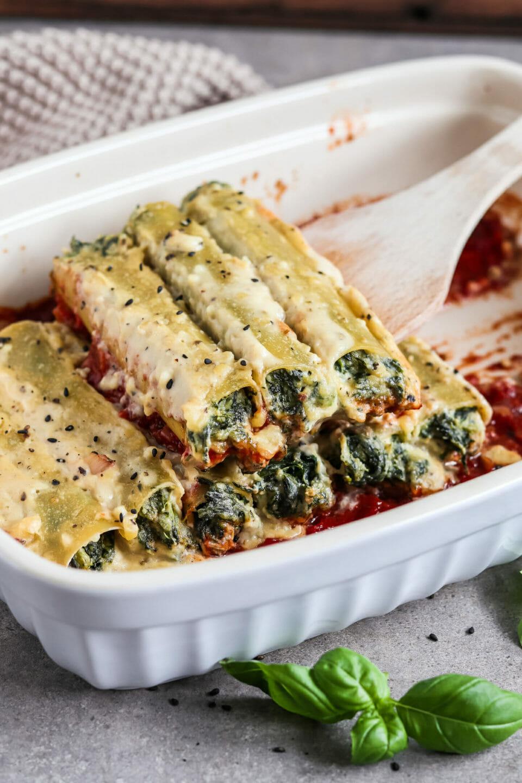 Mit Spinat Ricotta gefüllte Cannelloni aus dem Ofen mit Tomatensauce und Bechamelsauce, serviert in einer Auflaufform.