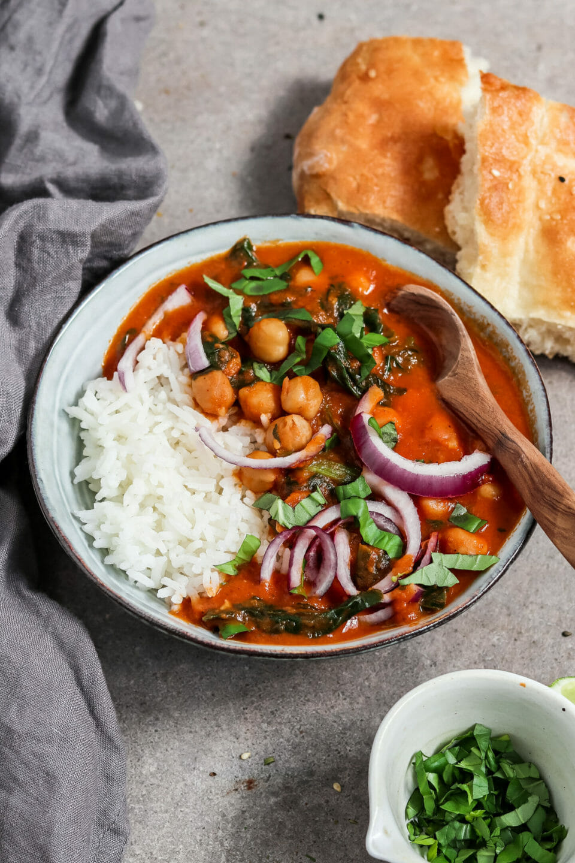 Veganes Kichererbsen Curry mit Spinat. Serviert mit Reis, Fladenbrot und roten Zwiebeln.