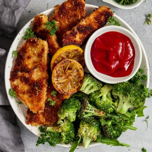 Vegane Sellerie Schnitzel serviert mit Brokkoli, Zitrone und Ketchup.