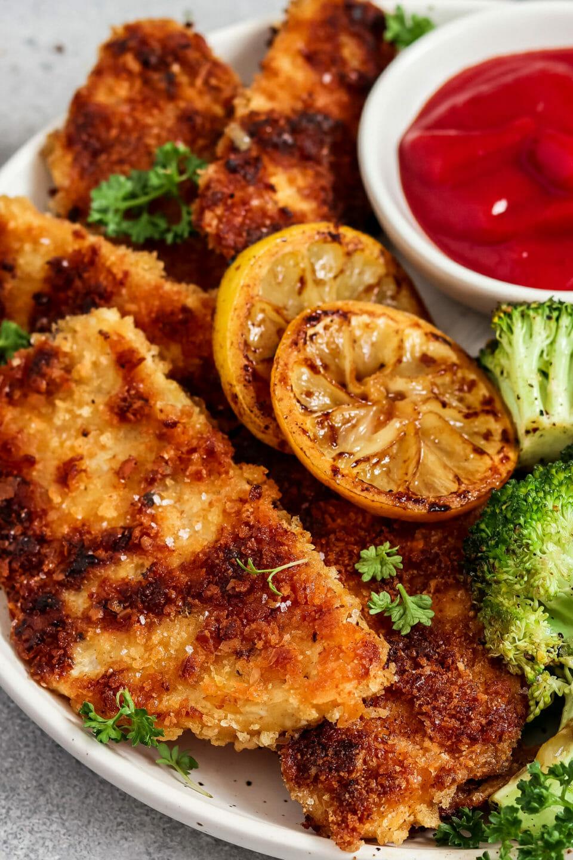 Vegane Schnitzel aus Sellerie. Serviert mit Brokkoli, Zitrone und Ketchup.