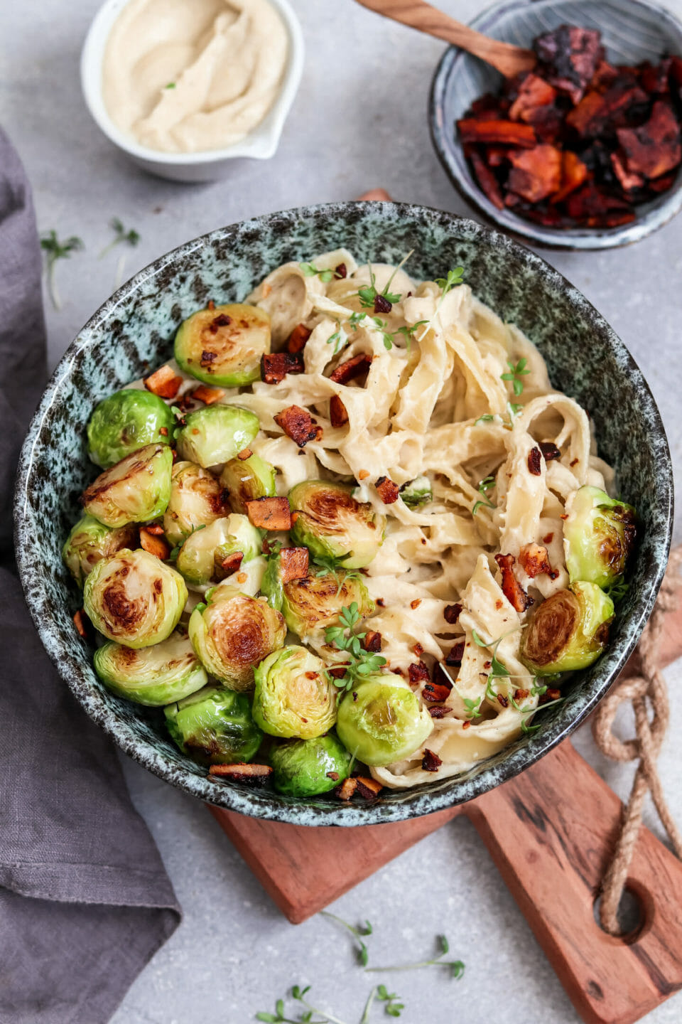 Vegan Fettuccine Alfredo made from cauliflower with brussel sprouts and bacon made from coconut chips.