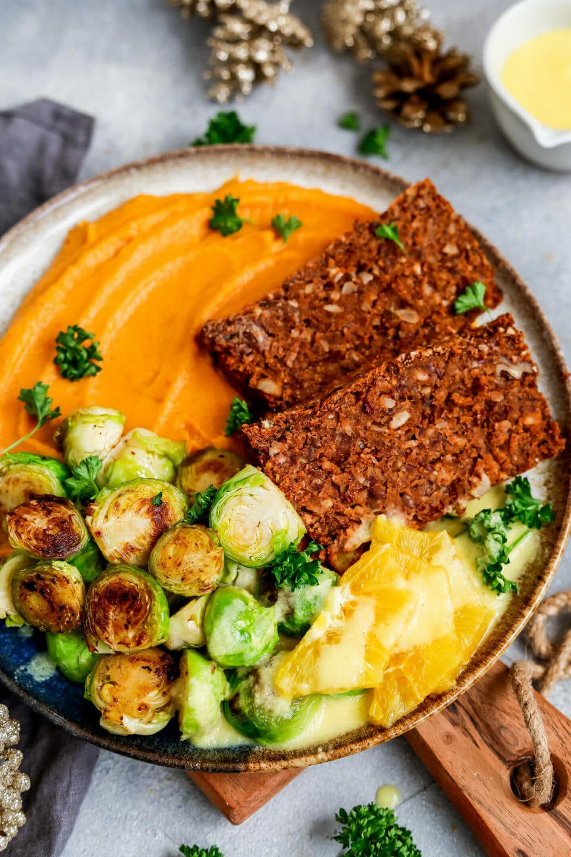 Veganer Nussbraten mit Süßkartoffelpüree, Rosenkohl und Orangen-Schalotten-Jus.