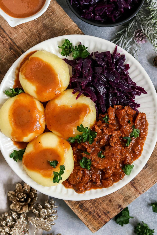 Veganes Gulasch mit Klöße und Apfel-Rotkohl.