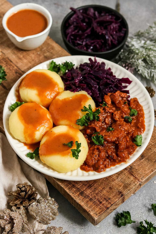 Schlesische Kluski mit veganem Gulasch, brauner Sauce und Apfel-Rotkohl.