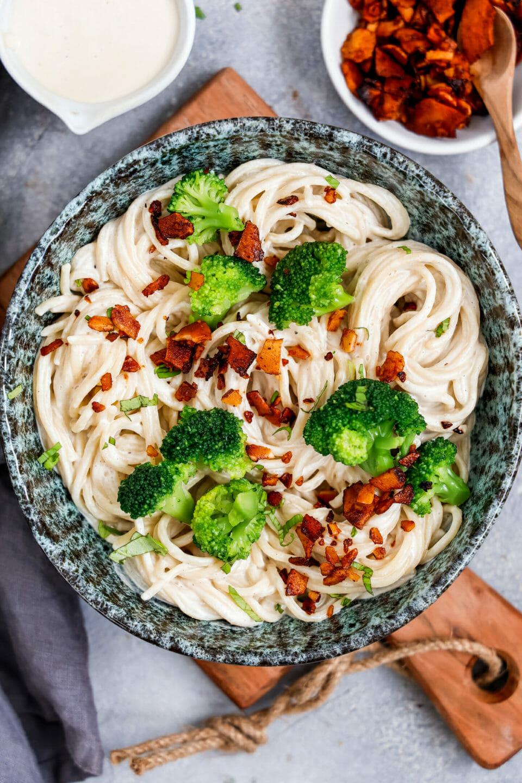 Vegane Spaghetti Carbonara angerichtet mit Kokos-Speck und etwas Brokkoli in einer Marmorfarbenen Schüssel auf Holzbrett