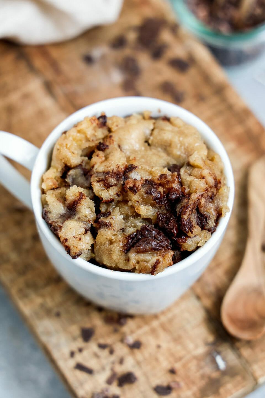 Ein Tassenkuchen oder auch Mug Cake mit Schokosplittern und Bananen serviert auf einem Holzbrett