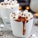 Eine Tasse mit veganer, heißer Kokos Schokolade garniert mit Sahne und Marshmallows