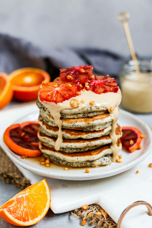 Vegane Orangen Mohn Pancakes aufgeschichtet auf einem hellen Teller und Marmorbrett