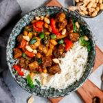 Veganes Tofu Kong Pao angerichtet in einer tiefen Schüssel auf einem Holzbrett