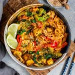 Veganes Thai Panang Curry in einer tiefen Schüssel auf einem Holzbrett serviert