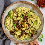 Veganes Avocado Pesto mit Nudeln, getrockneten Tomaten und Basilikum in einer tiefen Schüssel angerichet auf einem Holzbrett