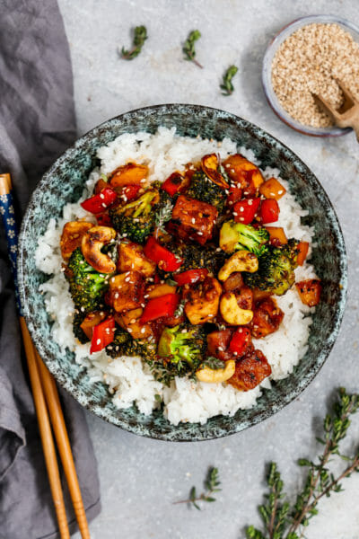 Cashew Sesam Tofu mit Gemüse, Sesam und Reis serviert in einer tiefen Schüssel