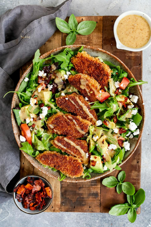 Veganer Honig-Senf Schnitzel Salat angerichtet in einem tiefen Teller auf hölzernem Untergrund