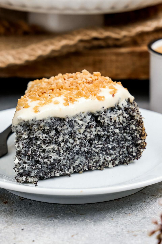 Mohnkuchen mit Vanillecreme, angerichtet auf einem flachen Teller, der ganze Kuchen auf einem Ständer im Hintergrund