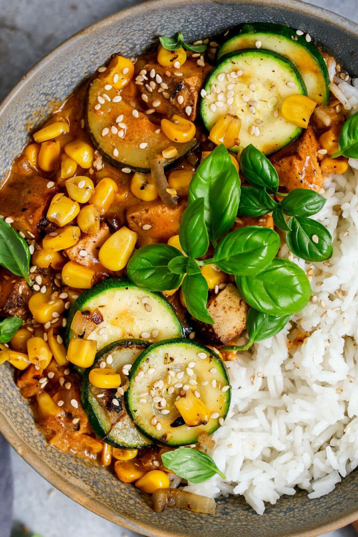 Veganes Kokos Curry angerichtet mit Reis in einer tiefen Schüssel auf einem Holzbrett