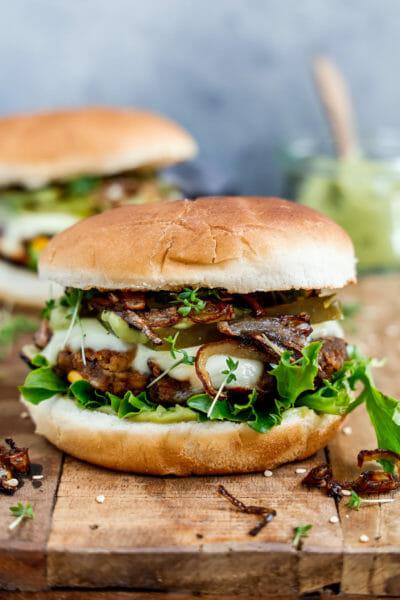 Vegane Burger Patties in einem leckeren Burger serviert auf einem Holzbrett