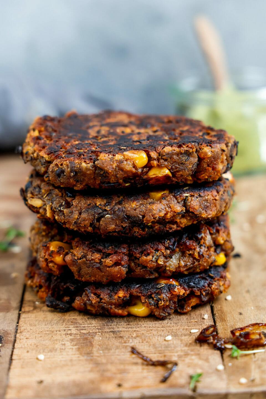 Vegane Burger Patties aufgestapelt und angerichtet auf einem Holzbrett