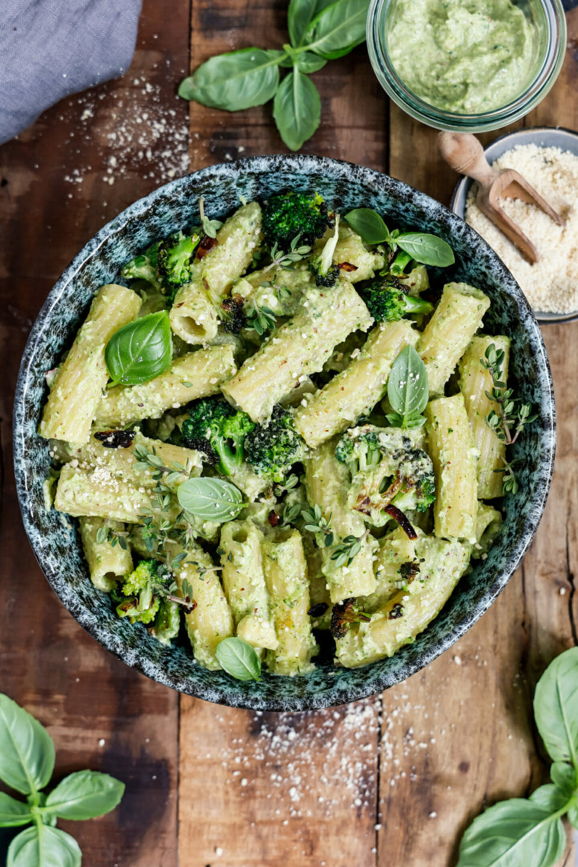 Veganes Brokkoli Pesto mit Pasta serviert in einer tiefen Schüssel auf einem hölzernen Brett