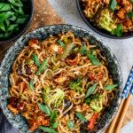 Vegane Asiatische Nudelpfanne in einem tiefen Teller auf einem Holzbrett serviert