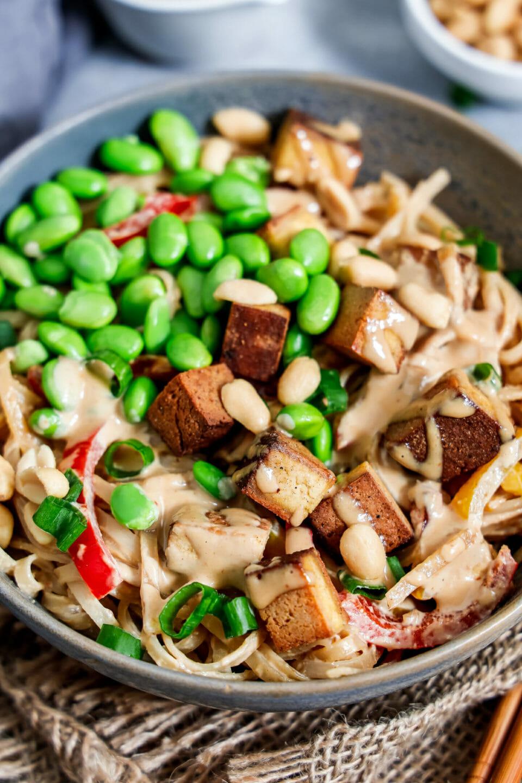 Vegane Thai Nudelpfanne mit Tofu, Gemüse und Erdnusssauce angerichtet in einem tiefen Teller